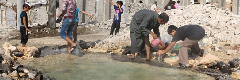 On 20 August 2016 in the Syrian Arab Republic, children and men collect water near a burst water pipe, after it was damaged by fighting in the Sheikh Saeed neighbourhood in eastern Aleppo.